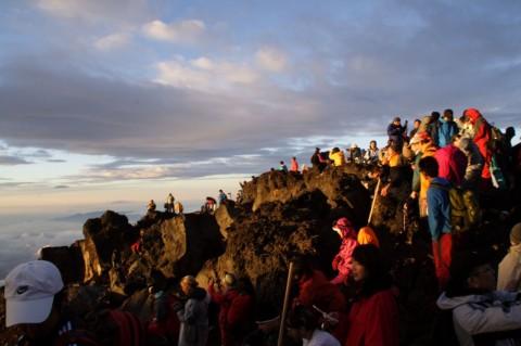 富士山山頂にてご来光を拝む人々